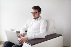 Il giovane in vetri controlla la sedia di seduta della posta mentre per mezzo del computer portatile Priorità bassa bianca Immagini Stock