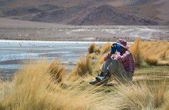 Il giovane viaggiatore femminile sta utilizzando il binocolo per vedere i fenicotteri Immagini Stock