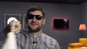 Il giovane vlogger maschio attivamente parla ed oscilla la borsa bianca alla macchina fotografica con il sorriso stock footage