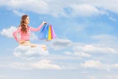 Il giovane volo femminile sulla nuvola e sulla tenuta insacca contro il cielo nuvoloso Fotografia Stock Libera da Diritti
