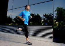 Il giovani funzionamento ed addestramento attraenti dell'uomo sul fondo urbano della via sull'allenamento dell'estate nello sport Fotografie Stock