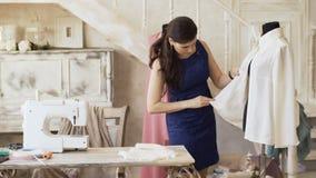 Il giovani progettista e cucitrice dell'abbigliamento controllano la camicia nello studio del sarto stock footage