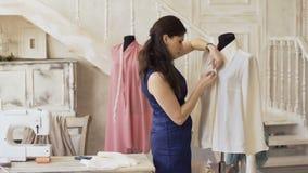 Il giovani progettista e cucitrice dell'abbigliamento cucono la camicia con il filo e l'ago nello studio del sarto stock footage