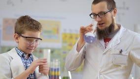 Il giovani scienziato ed assistente fa gli esperimenti con ghiaccio secco archivi video