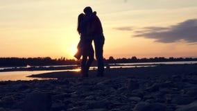 Il giovani tipo e ragazza abbracciano e bacio, contro lo sfondo di bello tramonto dal fiume HD, 1920x1080 lento archivi video