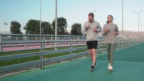 Il giovani tipo e ragazza stanno correndo sullo stadio e stanno chiacchierando durante l'allenamento archivi video
