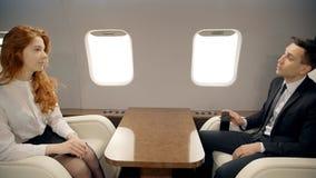 Il giovani uomo d'affari e donna di affari sono parlare, sedentesi nell'interno dell'aeroplano durante il volo stock footage