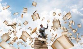 Il giovani uomo d'affari o studente che studiano la scienza e libri volano intorno Fotografia Stock