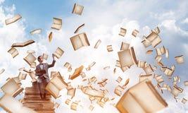 Il giovani uomo d'affari o studente che studiano la scienza e libri volano intorno Fotografie Stock