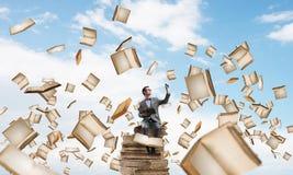 Il giovani uomo d'affari o studente che studiano la scienza e libri volano intorno Immagine Stock
