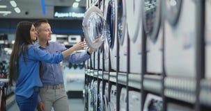 Il giovani uomo e donna della coppia sposata nel deposito degli apparecchi scelgono di comprare una lavatrice per la casa Apra il stock footage