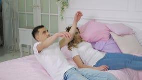 Il giovani uomo e donna delle coppie stanno cadendo sul letto, movimento lento archivi video