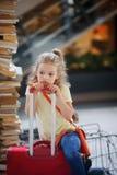 Il girlie affascinante 7-8 anni si siede accanto ai loro bagagli alla stazione Fotografie Stock