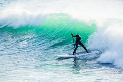 Il giro del surfista sopra sta sul bordo di pagaia sulla grande onda dell'oceano Stia sull'imbarco della pagaia nell'oceano fotografia stock libera da diritti