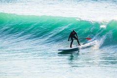 Il giro del surfista sopra sta sul bordo di pagaia sulle onde di oceano Stia sull'imbarco della pagaia nel mare immagini stock