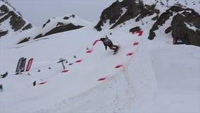 Il giro dello Snowboarder sull'alto trampolino, facente lancia in aria Stazione sciistica Montagne stock footage