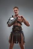 Il gladiatore in armatura che mostra il cuore cede firmando un documento il grey Fotografia Stock Libera da Diritti
