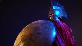 Il gladiatore romano in armatura di cuoio, casco ed impermeabile rosso è coperto di schermo rotondo e colpisce con una spada, len archivi video