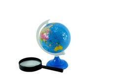 Il globo e la lente d'ingrandimento Immagine Stock