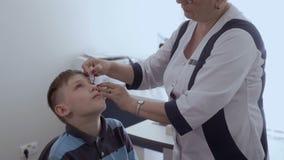 Il gocciolamento dell'oftalmologo cade negli occhi del ragazzino stock footage