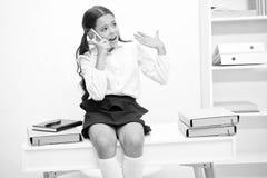 Il gossip è il suo elemento Il fronte sorridente della scolara discute i pettegolezzi freschi con i compagni Scuola d'informazion fotografie stock libere da diritti