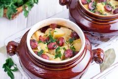 Il goulash della patata bollente con bacon e le salsicce viennesi è servito in una ciotola ceramica con sopra una tavola fotografie stock