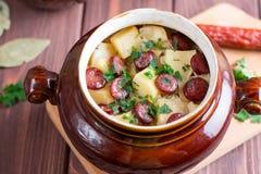 Il goulash della patata bollente con bacon e le salsicce viennesi è servito in una ciotola ceramica con sopra una vecchia tavola  fotografia stock libera da diritti