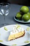 Il grafico a torta della calce chiave sul panno grigio con il vetro di vino e le calce dentro appoggiano fotografia stock