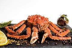 Il granchio di Kamchatka si trova su un piatto con le spezie immagini stock
