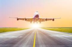 Il grande aereo passeggeri decolla dalla pista prima della luce dal sole Fotografie Stock