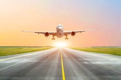 Il grande aereo passeggeri decolla dalla pista prima della luce dal sole Immagine Stock