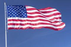 Il grande americano U.S.A. della bandiera stars il cielo blu del palo delle bande ventoso Fotografia Stock Libera da Diritti