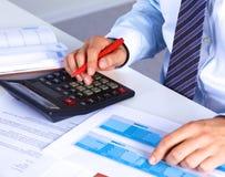 Il grande capo controlla i calcoli su un calcolatore fotografia stock libera da diritti