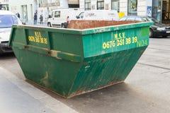 Il grande contenitore di rifiuti verde sta su un bordo della strada Immagini Stock