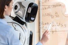 Il grande cyborg sta lavorando nell'ufficio con la giovane donna elegante Fotografia Stock Libera da Diritti
