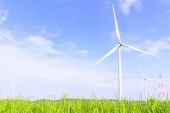 Il grande giacimento della turbina del mulino a vento con l'erba Fotografie Stock Libere da Diritti
