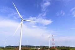 Il grande giacimento della turbina del mulino a vento ed il pilone di elettricità Fotografia Stock Libera da Diritti