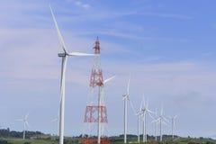 Il grande giacimento della turbina del mulino a vento ed il pilone di elettricità Fotografie Stock Libere da Diritti