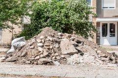 Il grande mucchio del calcestruzzo e della sporcizia del cemento sulla via davanti all'edificio residenziale ha andato come resti Immagine Stock Libera da Diritti