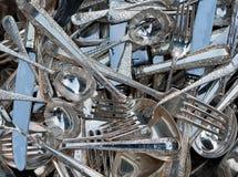 Il grande mucchio della tavola e dei cucchiaini d'argento, le forcelle ed i coltelli hanno sparso sulla tavola Immagini Stock Libere da Diritti