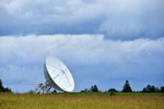 Il grande riflettore parabolico nel campo per la ricezione e la trasmissione il segnale e del trasferimento di dati della TV al s fotografia stock libera da diritti