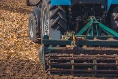 Il grande trattore che tira un aratro ed ara il campo, rimuove i resti del cereale precedentemente smussato Fotografia Stock