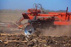 Il grande trattore che tira un aratro ed ara il campo, rimuove i resti del girasole precedentemente smussato Fotografia Stock Libera da Diritti