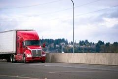 Il grande trattore moderno rosso del camion dei semi dell'impianto di perforazione che trasporta l'annuncio pubblicitario va Immagine Stock