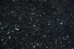 Il granito naturale di colore scuro con gli scintilli luminosi sulla superficie, ha chiamato Emerald Pearl immagini stock