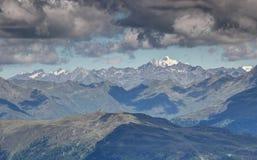 Il Gray si rannuvola i picchi nevosi alto Tauern Austria delle creste soleggiate Fotografia Stock