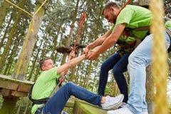 Il gruppo aiuta l'uomo a scalare le alte corde scorre fotografie stock libere da diritti
