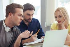 Il gruppo amichevole allegro sta utilizzando il computer in ufficio Fotografie Stock
