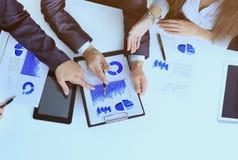 Il gruppo amichevole di affari ha analizzato i documenti - grafici e grafici fotografie stock