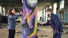 Il gruppo concentrato di donna e dell'uomo dei pittori urbani sta dipingendo i graffiti sulla casa vuota rovinata interno della c stock footage